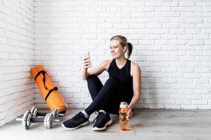 mulher fazendo selfie após o treino sentada no chão foto