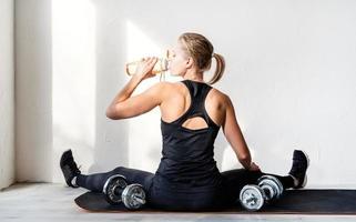 mulher malhando com halteres mostrando os músculos das costas e braços foto