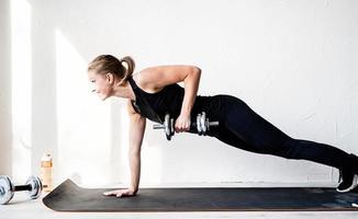 mulher fazendo exercícios levantando halteres, treinando costas e braços foto