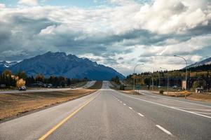 carro dirigindo em rodovia com montanhas rochosas no outono em canmore foto