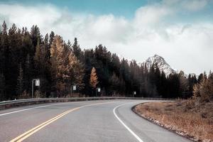 viagem de carro dirigindo em rodovia com montanhas rochosas e floresta de pinheiros no outono no parque nacional de banff foto