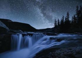 cotovelo cai com Via Láctea no céu noturno no parque nacional em Kananaskis foto