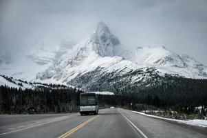 ônibus dirigindo em estrada de asfalto com grande fundo de montanha de neve foto