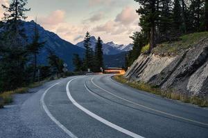 carro leve em rodovia com montanhas rochosas no parque nacional de banff foto