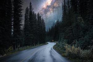 Via Láctea com estrelado sobre rodovia na floresta no parque nacional foto