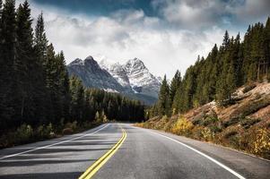 rodovia de asfalto e montanhas rochosas em uma floresta de pinheiros no parque nacional de banff, canadá foto