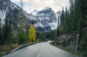 dirigindo na rodovia com montanhas rochosas na floresta de outono no Lago Moraine, Alberta foto