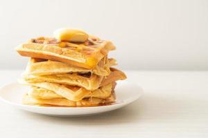 pilha de waffles com manteiga e mel foto
