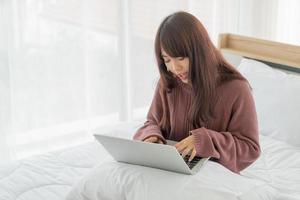 mulheres asiáticas trabalhando com laptop na cama foto