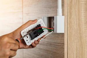 mão de um eletricista está usando uma chave de fenda para prender os fios ao soquete. foto