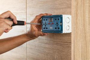 eletricista está usando uma chave de fenda para instalar uma tomada em uma caixa de plástico em uma parede de madeira. foto