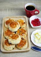 Feche o bolinho caseiro com geléia de morango e manteiga em fundos de mesa de madeira foto