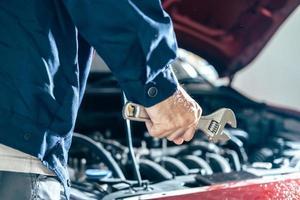 asiáticos homem médico proteger máscara de proteção máscara facial inspeção mecânica chave inglesa para consertar carro azul para seguro de manutenção de serviço com capô de motor de carro. para transporte automóvel automotivo foto