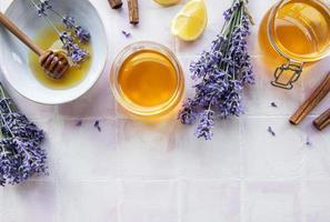 potes e tigela com mel e flores frescas de lavanda foto