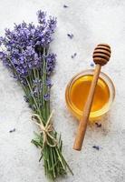 jarra com mel e flores frescas de lavanda foto