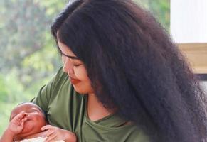 mãe está amamentando mãe gostava de brincar com seu filho recém-nascido feliz, o conceito de amor e laços familiares. foto