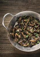 cogumelos shiitake salteados com alho e ervas em uma frigideira de metal foto