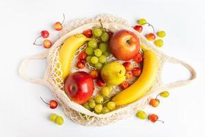 frutas maduras orgânicas em saco de malha ecológica em fundo branco. bolsa de barbante na moda para fazer compras. alimentação saudável e conceito de estilo de vida sustentável. desperdício Zero. foto