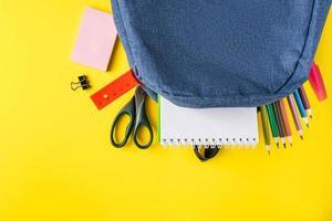 mochila escolar com material de escritório em fundo amarelo. lugar para texto. foto