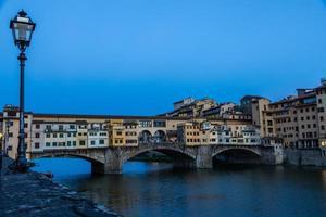 pôr do sol na ponte vecchio - ponte velha - em florença, itália. incrível luz azul antes do anoitecer. foto