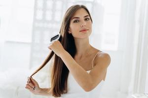 escova de cabelo. retrato de uma jovem mulher escovando cabelos lisos naturais com o pente. cintura para cima da menina, penteando o cabelo longo e saudável bonito com a escova de cabelo. conceito de cuidado e beleza para os cabelos foto