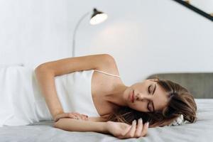 mulher dormindo. bela jovem com cabelos longos, deitada na cama e mantendo os olhos fechados enquanto dormia pela manhã. estilo de vida das pessoas e conceito de aparência feminina foto