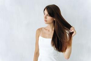 tão livre quanto o vento. retrato de mulher bonita encantadora está de pé e olhando para longe enquanto aprecia a qualidade de seus longos cabelos. fundo isolado foto