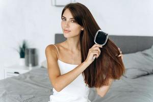 mulher morena saudável, escovando o cabelo com o pente antes da caminhada, enquanto está sentado no quarto e olhando para a câmera. conceito de procedimentos de autocuidado foto