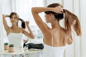 jovem mulher confiante vestindo roupas brancas domésticas, olhando para seu reflexo enquanto está sentado no espelho e escova o cabelo morena longa e saudável. fêmea milenar fazendo rabo de cavalo pela manhã foto