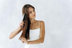 cuidar de chevelure. atraente mulher caucasiana, olhando para longe enquanto penteava o cabelo e se sentia satisfeita. estilo de vida, conceito de cuidados de beleza foto