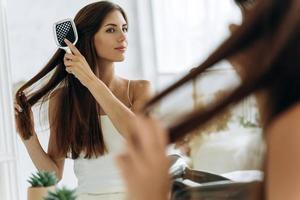 cintura para cima vista do retrato da mulher bonita feliz em roupa doméstica, penteando o cabelo na frente do espelho, segurando uma escova grande. foto