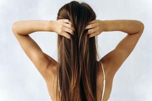 foto de vista traseira de uma jovem mulher bonita tocando cabelo castanho liso com as mãos isoladas no fundo de cor branca. conceito de cabelo de mulher
