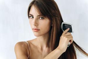 headshot portrait 25s alegre mulher segurando a escova de cabelo e arrumar seu cabelo forte e saudável depois de tomar um banho. estilo de vida de rotina de beleza matinal, tratamento para publicidade de crescimento de cabelo perfeito, cuidados com os cabelos foto