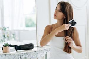 cintura para cima retrato de uma senhora radiante, penteando seus longos cabelos escuros enquanto desvia o olhar com um sorriso calmo. conceito de cuidado de cabelo. foto
