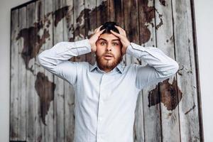 retrato de um homem com barba. ele agarra sua cabeça com espanto, seus olhos esbugalhados e olhando para a câmera - imagem foto