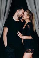 casal feliz esperando bebê posando em fundo escuro, perfil foto