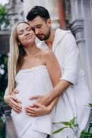 marido abraça esposa grávida de costas na varanda foto
