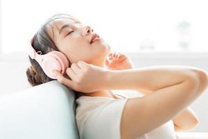 retrato de uma jovem sentada no sofá reclinada e tanaj curtindo música foto
