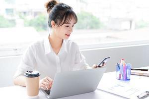 retrato de uma jovem empresária sentada e usando o telefone foto