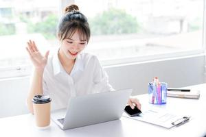 retrato de uma jovem empresária sentado e fazendo videochamadas com amigos foto