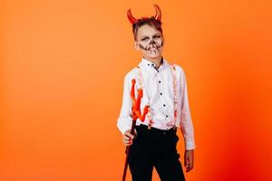 menino diabo em pé meia-volta contra um fundo laranja em maquiagem de baile de máscaras. conceito de halloween foto