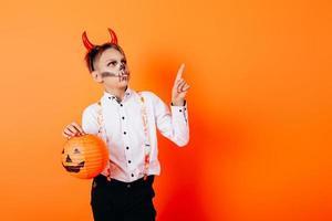 rapaz com maquiagem de máscaras de diabo segurando uma abóbora e apontando para cima. conceito de halloween foto