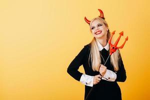 emoção feliz da mulher do diabo em pé contra um fundo amarelo. foto