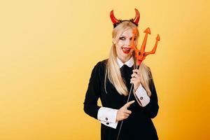 mulher diabo em pé contra um fundo amarelo e mostrando a língua foto