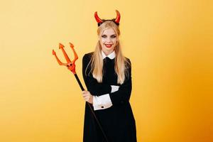 mulher diabo em pé contra um fundo amarelo foto