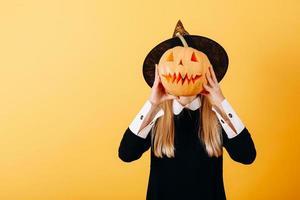 mulher em pé contra um fundo amarelo segurando uma abóbora e escondendo o rosto foto