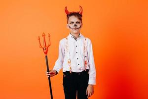 menino diabo em pé contra um fundo laranja em maquiagem de baile de máscaras. conceito de halloween foto