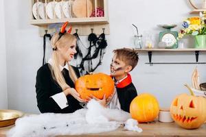 mãe e filho segurando uma abóbora durante os preparativos para o halloween. foto