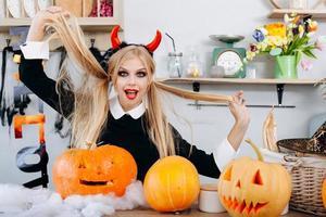 mulher diabinha engraçada sentada à mesa ao lado de uma brincadeira de abóboras. - conceito de halloween foto