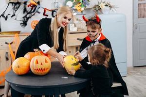mãe e filhos desenhando na abóbora, brincam e se divertem em casa. - conceito de Halloween foto